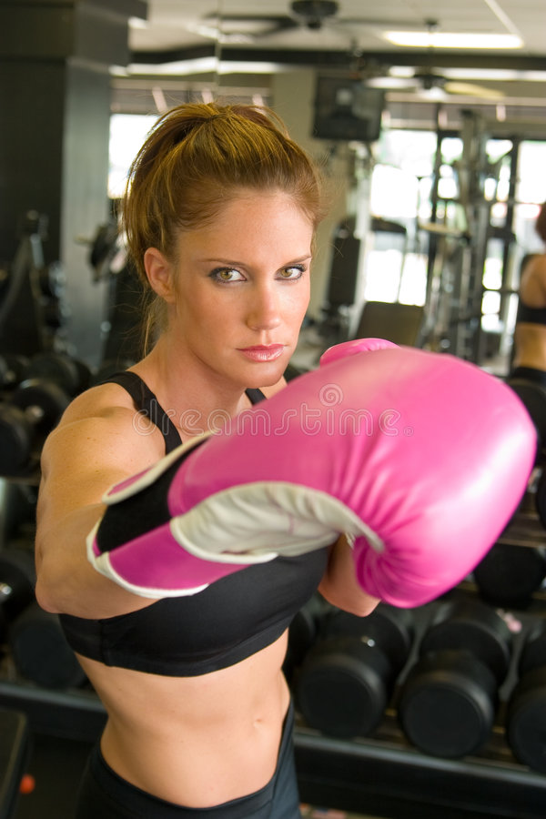 Woman In Pink Boxing Gloves 6. Beautiful, fit woman wearing hot pink boxing gloves stock images