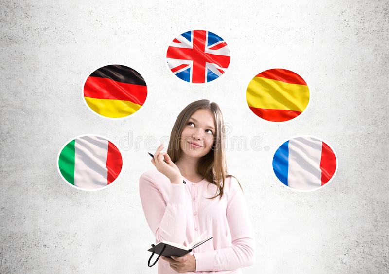 Woman in pink and country flags. Portrait of a young woman wearing a pink cardigan while standing near a concrete wall with European country flags drawn on it royalty free stock image