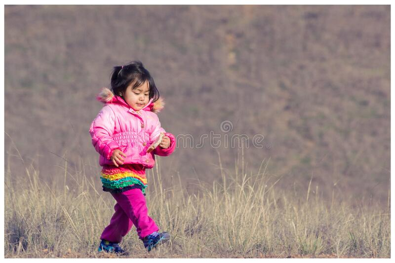 Woman In Pink Down Jacket Walking On Green Grass During Daytime Free Public Domain Cc0 Image