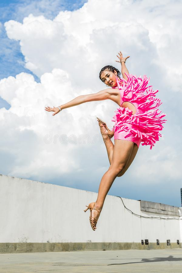 Woman in Pink Dress Doing Jump Shot While Extending Arms Under White Clouds royalty free stock photos