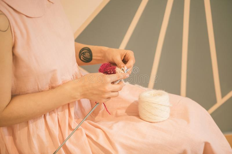 Woman in pink dress knitting. hobby crafts things. Horizontal composition royalty free stock images