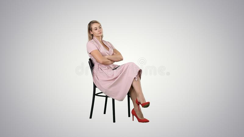 Woman in pink dress sitting on a chair waiting for someone on gradient background. Professional shot in 4K resolution. 005. You can use it e.g. in your stock images