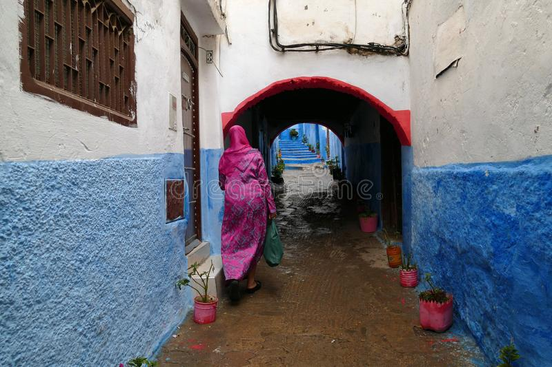 Woman with pink dress walking in a little colorful alley, medina of Tétouan, North of Morocco, Africa stock images