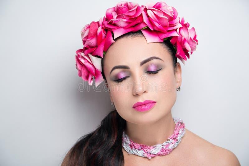 Woman pink flower wreath bright make up. Beautiful woman wearing massive flower wreath. Long black hair ponytail. Professional cosmetics makeup. Velvet lipstick stock images
