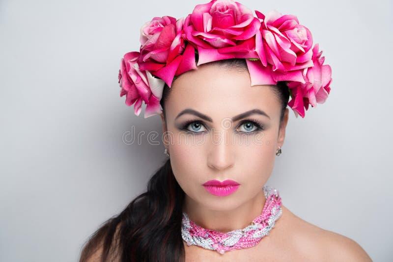 Woman pink flower wreath bright make up. Beautiful woman wearing massive flower wreath. Long black hair ponytail. Professional cosmetics makeup. Velvet lipstick stock photo