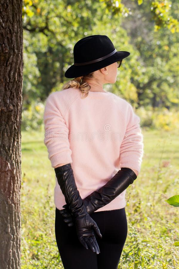 A woman in long gloves stands back royalty free stock image