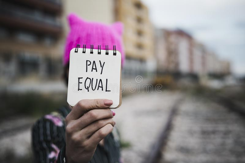Woman with a pink hat and the text pay equal. Closeup of a young woman outdoors, wearing a pink pussycat hat, showing a piece of paper in front of her face with stock photos