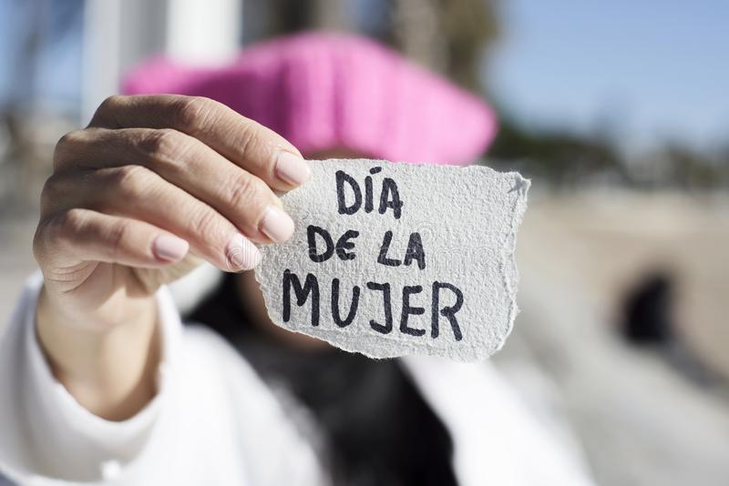 Woman with pink hat and text womens day in spanish. Closeup of a young woman outdoors wearing a pink hat showing a piece of paper in front of her face with the stock image