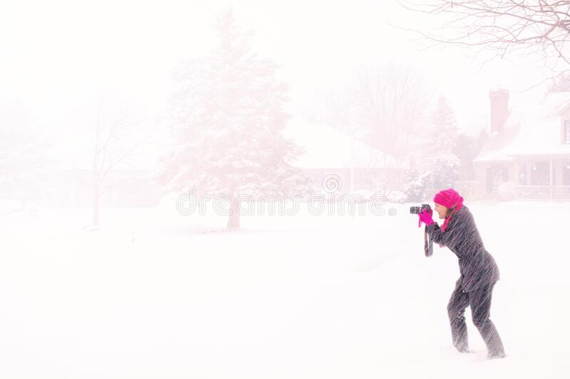Woman In Pink Hijab Holding Black Dslr Camera Under Raging Snow During Daytime Free Public Domain Cc0 Image