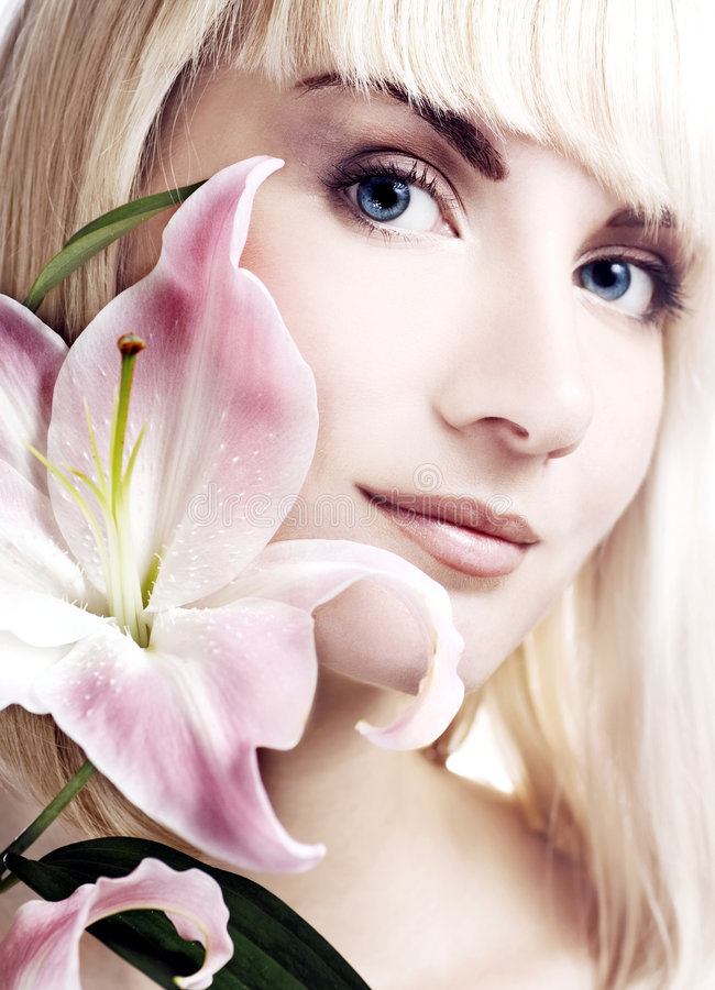 Woman with pink lily. Beautiful woman with pink lily high-key portrait royalty free stock photography