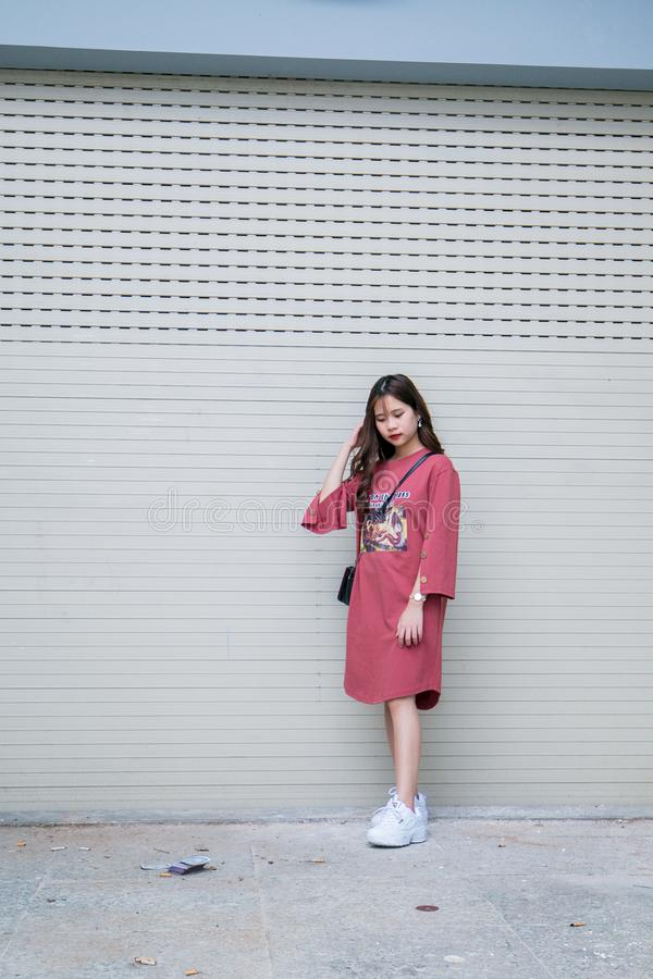 Woman in Pink Long-sleeved Midi-dress and Pair of White Shoes royalty free stock images