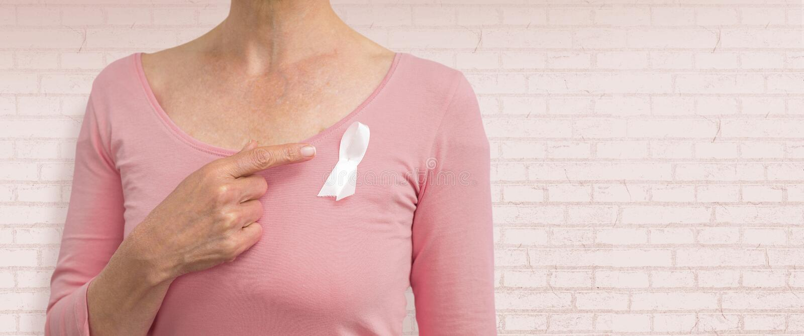 Composite image of woman in pink outfits showing ribbon for breast cancer awareness royalty free stock image