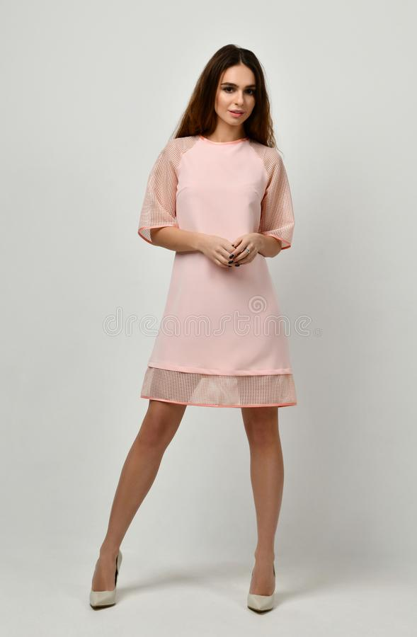 Woman in pink pastel color winter dress standing stock image