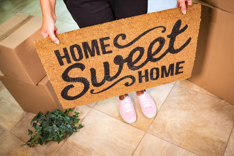 Woman in Pink Shoes Holding Home Sweet Home Welcome Mat, Boxes and Plant stock images