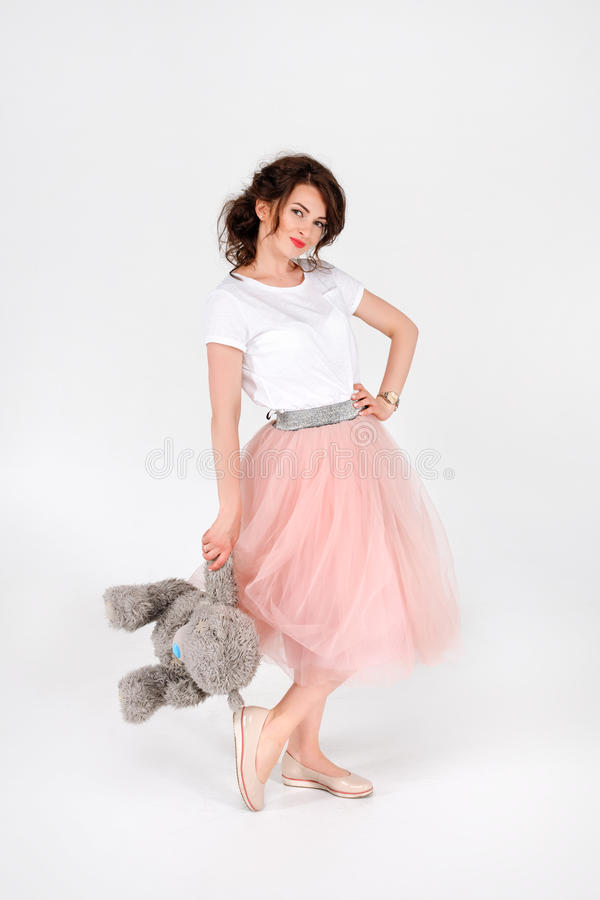 Woman in pink skirt holding big soft teddy bear on white background. Beautyful smiling young woman in pink skirt holding big soft teddy bear on white background royalty free stock image