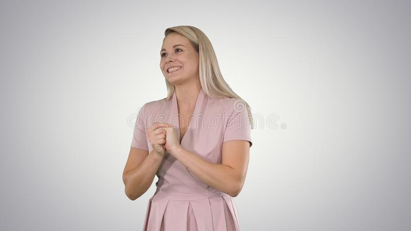 Woman in pink talking to the camera on gradient background. royalty free stock photography