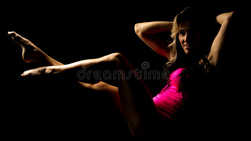 Woman in pink tank and shorts hands behind head highlighted stock photography