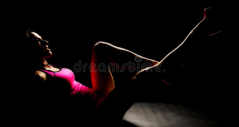 Woman in pink tank and shorts and heels sit back leg up stock photo