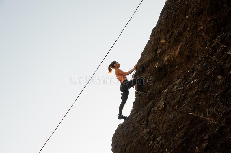 Woman equipped with a rope climbing on the sloping rock stock photos