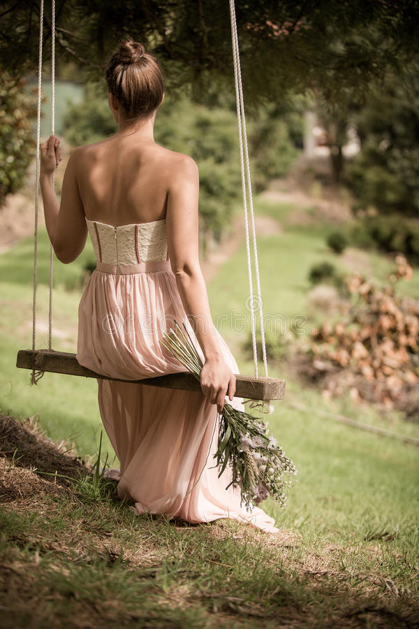 Woman In Pink Tube Dress Sitting On A Swing Holding A Flower Free Public Domain Cc0 Image