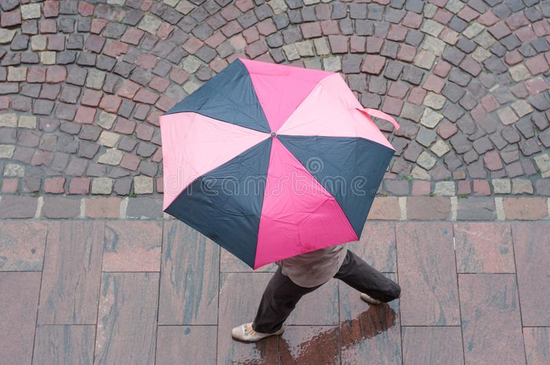 Woman with pink umbrella on cobbles place royalty free stock images