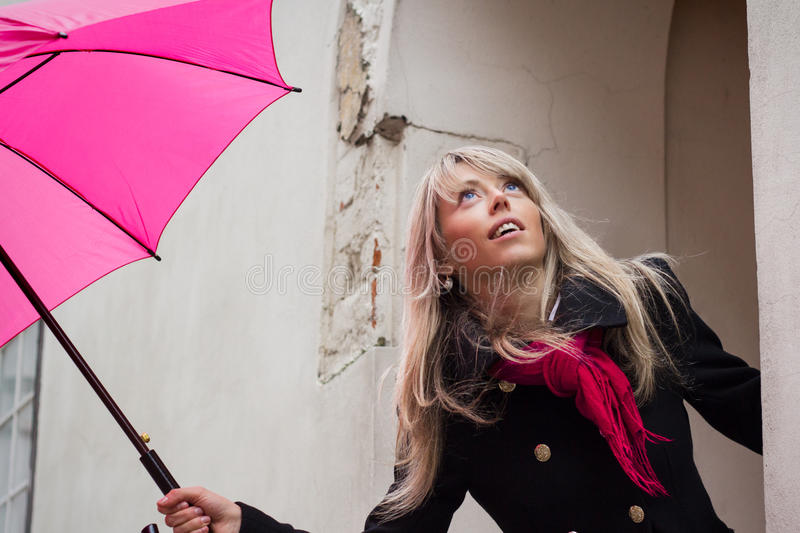 Woman with pink umbrella. In front of a house royalty free stock photography