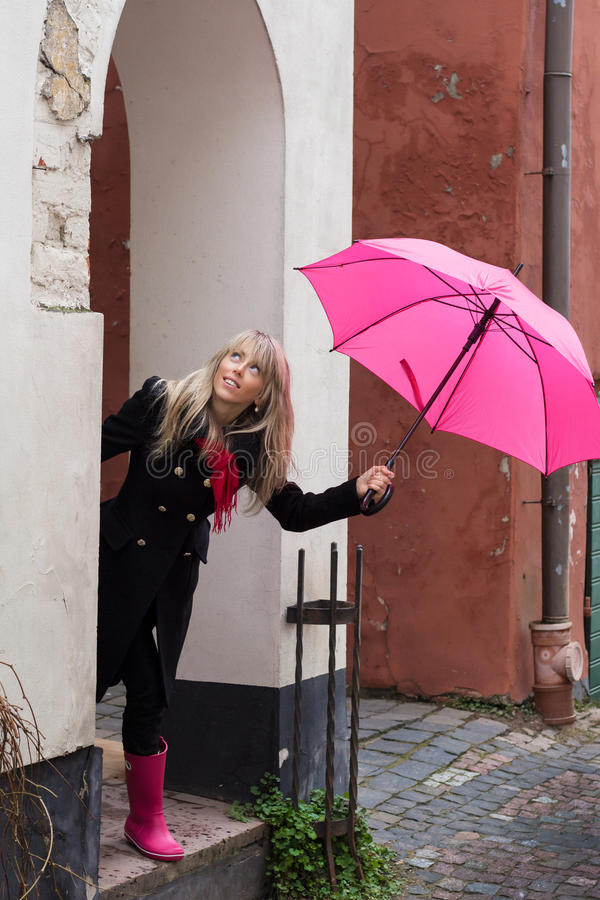 Woman with pink umbrella. Looking up in front of a house royalty free stock image
