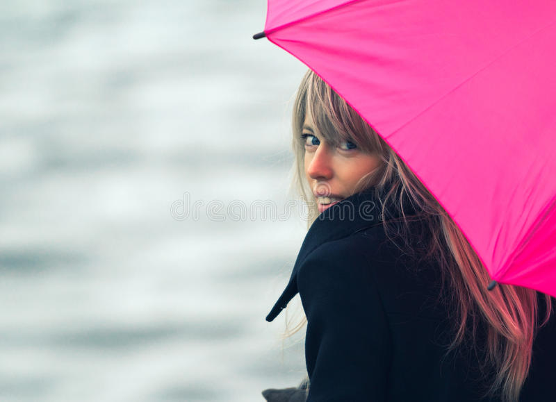 Woman with pink umbrella. Portrait of young woman with pink umbrella stock photos