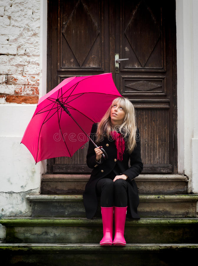 Woman with pink umbrella. Sitting on stairs in front of a house stock photography