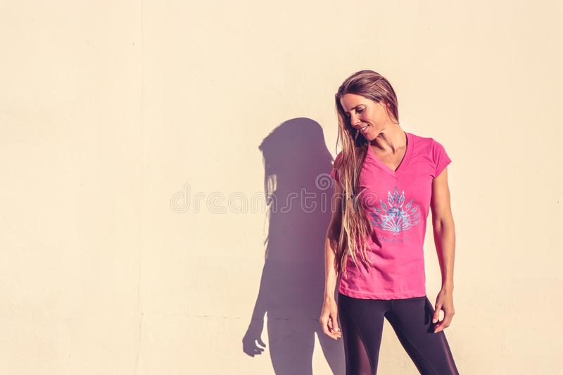 Woman in Pink V-neck Cap-sleeved Shirt Standing Near Wall royalty free stock images