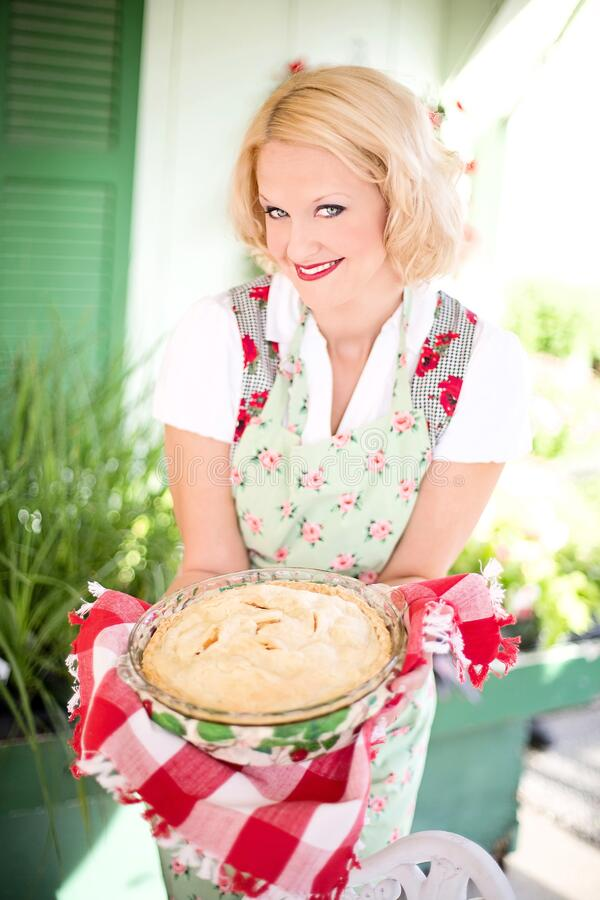 Woman in Pink White Floral Apron Smiling While Holding a White Creme Food during Daytime stock photos