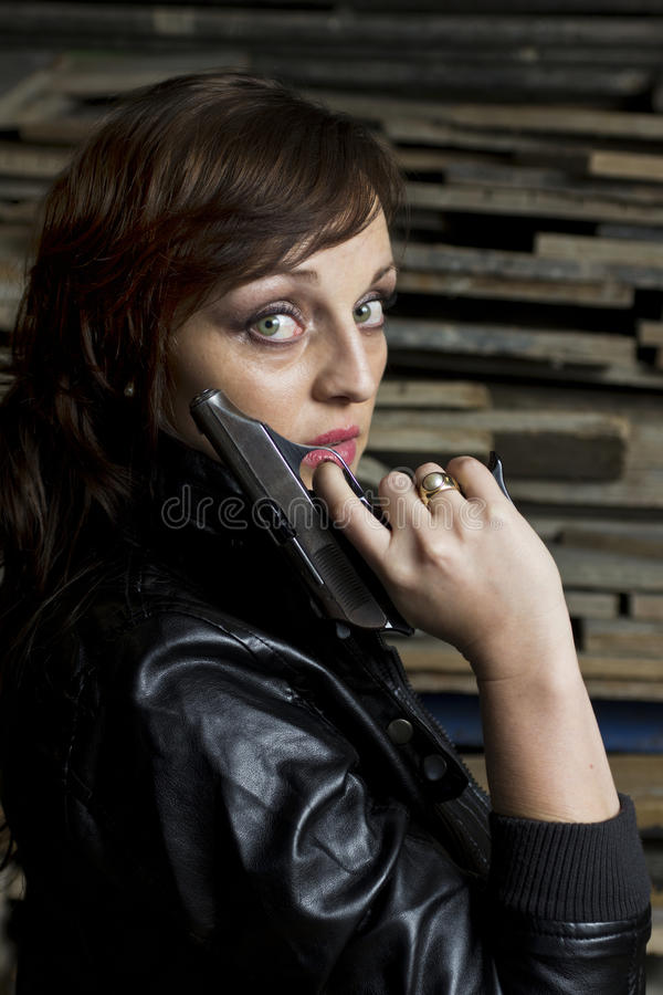 Woman with pistol and leather jacket stock images