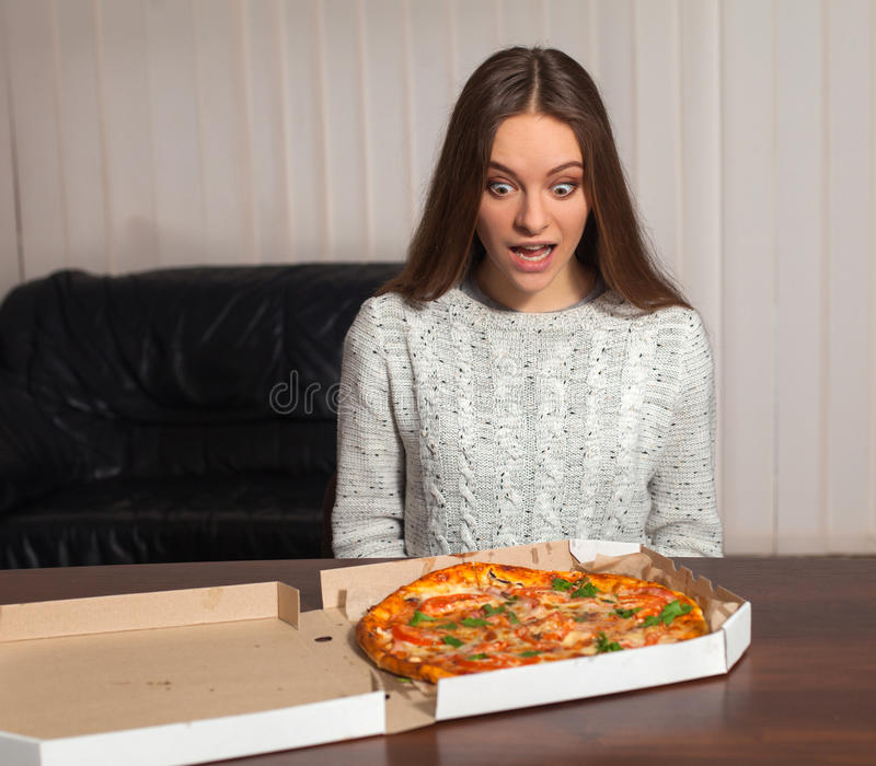 Woman with pizza. Young woman is sitting and going to eat pizza royalty free stock photo