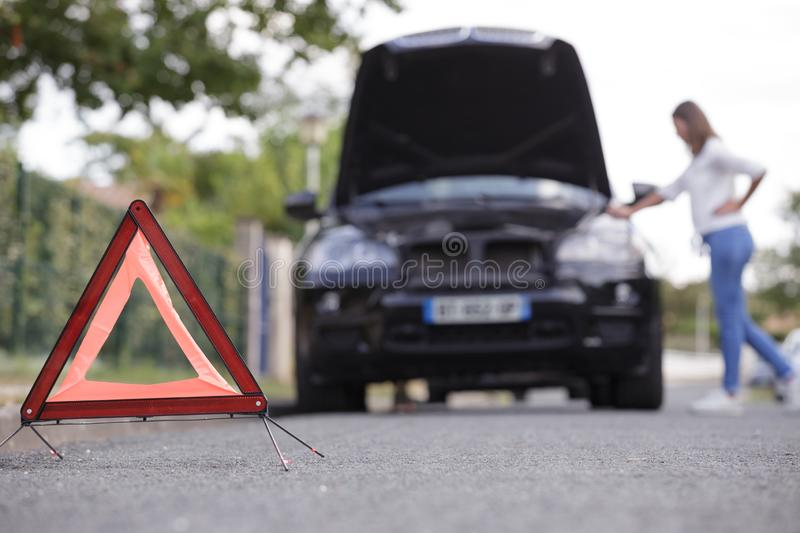 Woman after placing emergency warning triangle sign stock photos