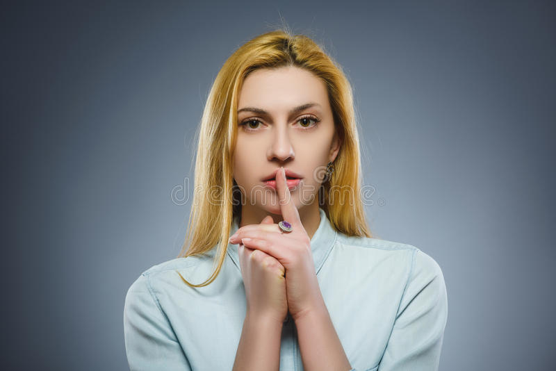 Woman placing finger on lips asking shh, quiet, silence on gray background stock image