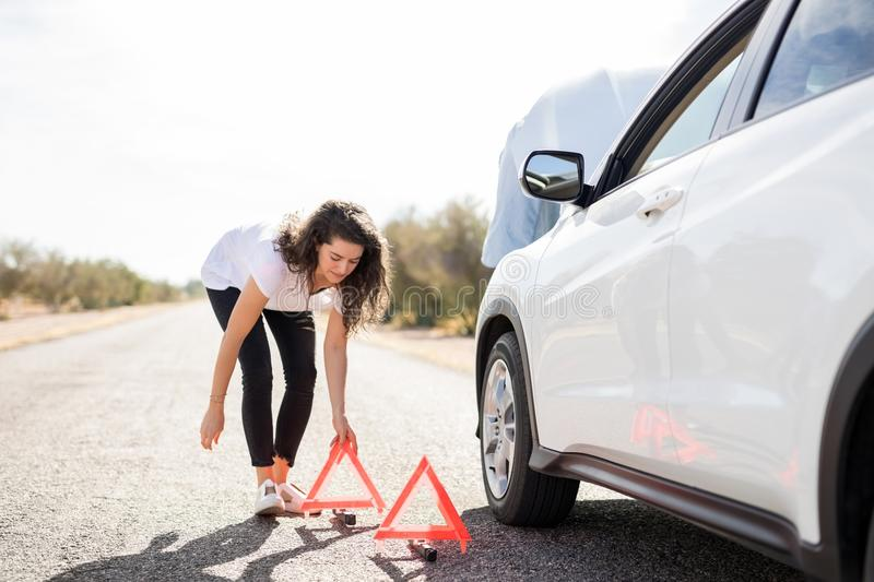 Woman placing red warning sign by broken car stock photo