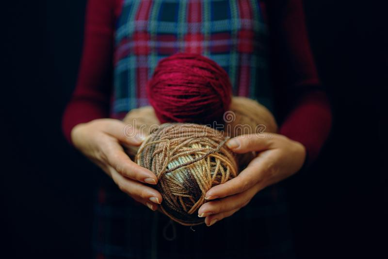 Woman holds balls of thread. Woman in a plaid dress and a red sweater holds several colored balls of thread royalty free stock images