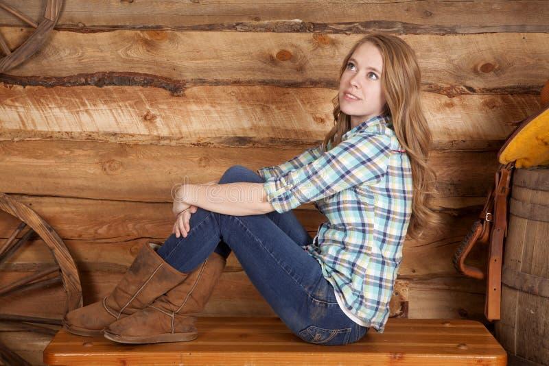 Woman plaid shirt sit side legs up wood stock photo
