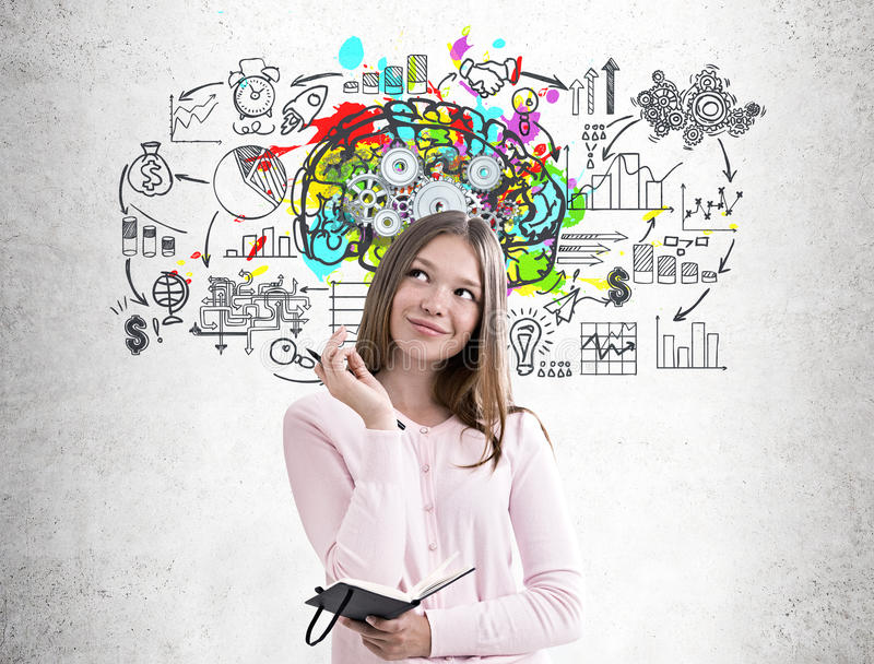 Woman with a planner, colorful brain cogs. Portrait of a dreamy girl in a pink sweater holding a planner and a pen and standing near a concrete wall wall with a stock photo