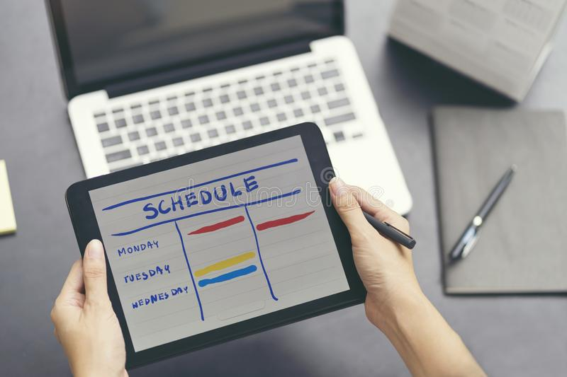 Woman planning agenda and schedule using calendar event planner. royalty free stock images