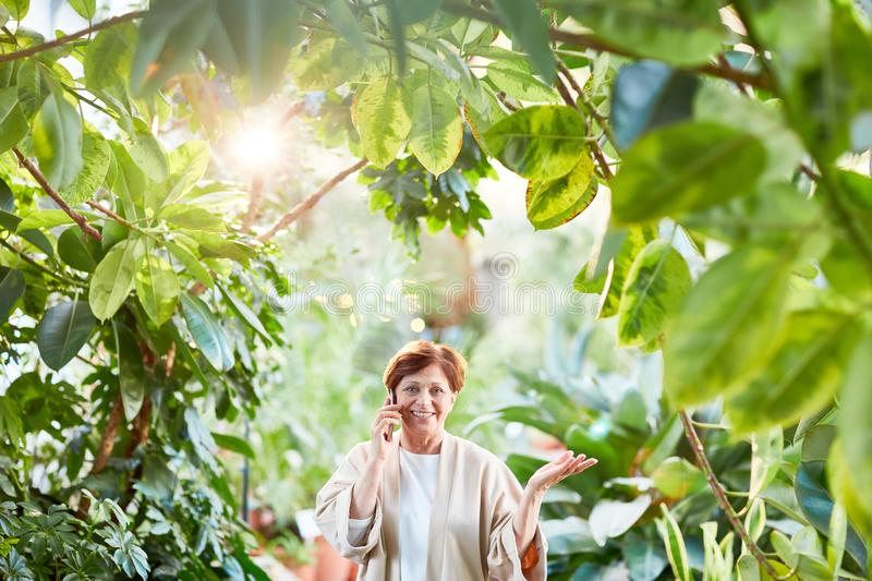 Woman in plants. Happy aged woman decided to go for walk in her home garden or orangery while calling her children or husband royalty free stock photos