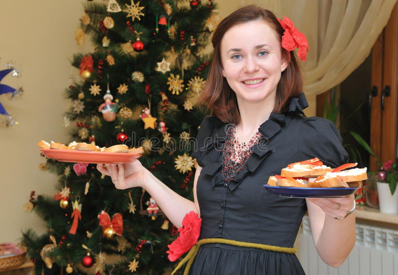 Woman with plate near Christmas-tree stock image