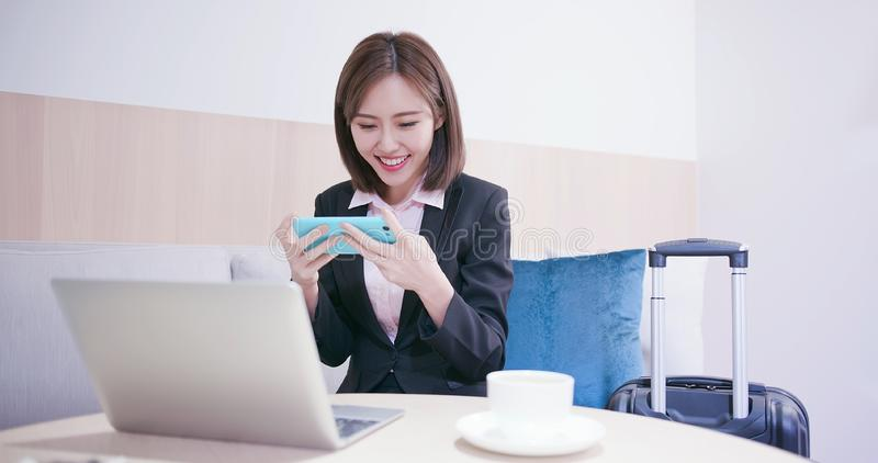 Woman play mobile game happily. On her business trip stock photo