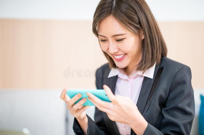 Woman play mobile game happily. By smartphone stock photo