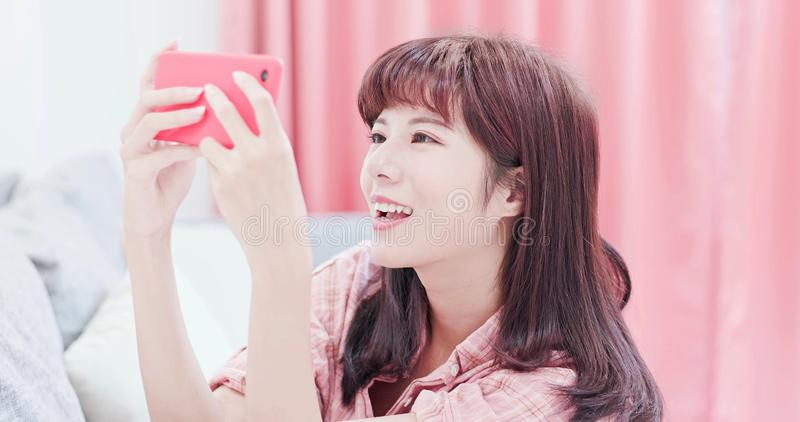 Woman play mobile game. By smart phone happily and sit on the sofa at home royalty free stock images