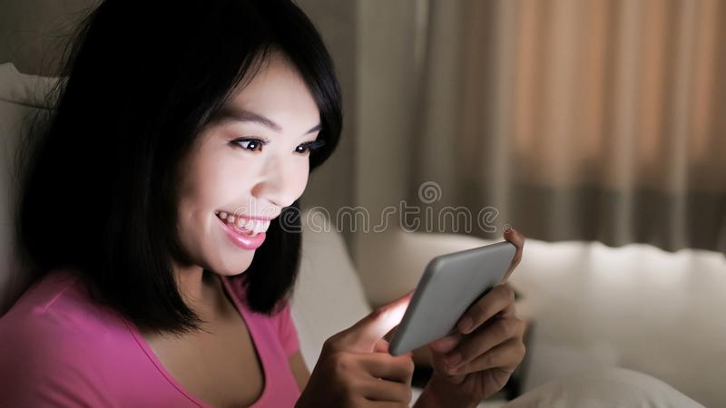 Woman play mobile game. Happily in the evening royalty free stock photos