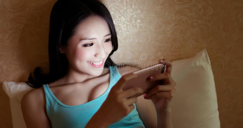Woman play phone happily. On the bed in the evening stock photography