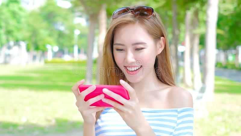 Woman use phone. Woman play phone and mobile game in the park royalty free stock photos