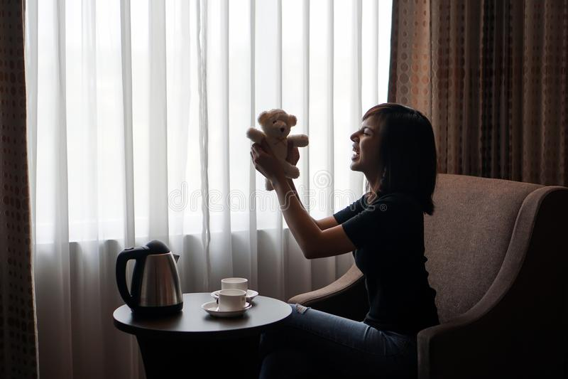 Woman play with teddy bear doll toy in hotel room royalty free stock photography