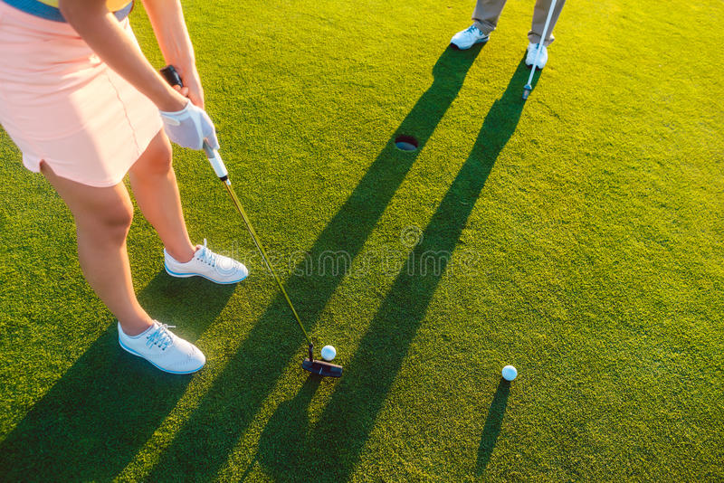 Woman player ready to hit the ball into the hole at the end of a royalty free stock photography